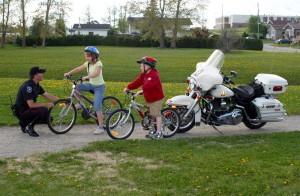 Police officer greeting kids on bicycles.